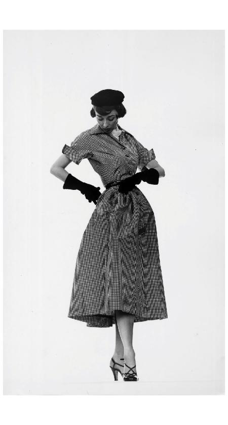 Model Dorian Leigh wearing pin-point taffeta dress w. full skirt by Mollie Parnis, long black gloves 1950 Photo Gjon Mili