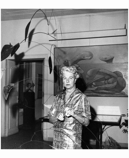 American art collector and millionairess Peggy Guggenheim (1898 - 1979) in her eighteenth century Venetian palace. Hanging from the ceiling is a 1941 Alexander Calder mobile and behind her is a 1937 painting by Picasso