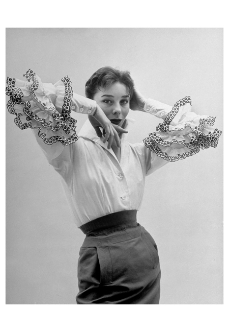 Bettina High buttoned cuffs with black-embroidered ruffles falling over them are one of many De Givenchy treatments of big sleeve, an important fashion this season 1952 Photo Nat Farbman