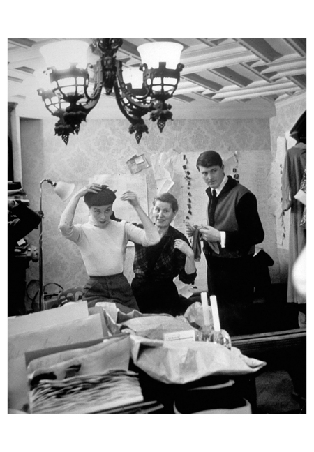 Designer de Givenchy (right) and fitter study effect in a mirror of hat tried on by his partner Bettina between her publicity chores Photo Nat Farbman