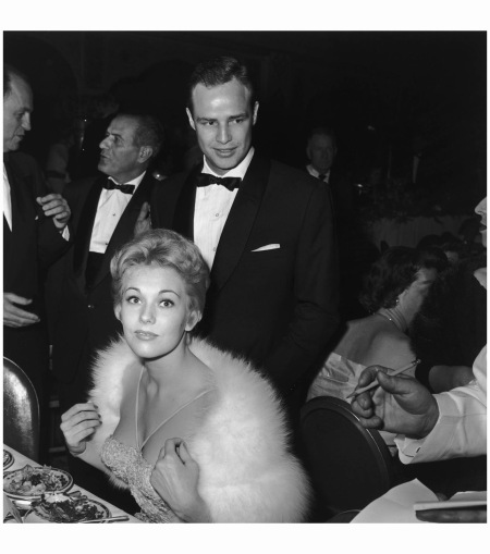 Kim Novak, wearing a fur stole, and Marlon Brando, wearing a tuxedo, sit and stand at an awards dinner 1950's