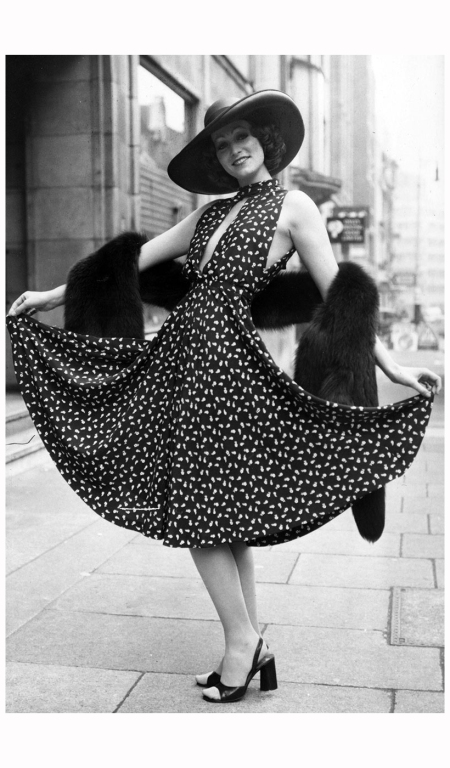 Model Marion Cameron in a Christian Dior navy crepe de chine dress with tiny floral print and slashed bodice. Her broad brimmed hat of navy straw is also by Dior 1974 Frank Barratt