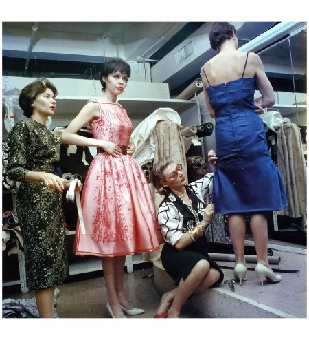 Pauline Trigere (seated) fits a dress on a model while Gigli's wife Sue Ellen tries on a pink dress, photo by Ormond Gigli, 1962