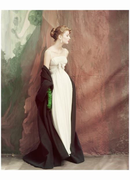 Suzy Parker wears a strapless white chiffon dress, its Empire waist banded with rhinestones, paired with an emerald green cloak by Gunther Jaeckel Vogue oct 1953 John Rawlings