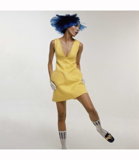 Kellie Wilson wearing yellow Courrges cotton dress, plunged at the neck with rounded pockets. On her head she is wearing a purple dutch-boy wig and on her feet white bobby socks and black patent leather shoes 1969 - Bert Stern