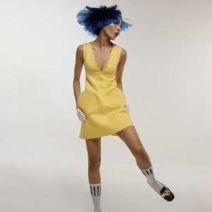 Kellie Wilson wearing yellow Courrges cotton dress, plunged at the neck with rounded pockets. On her head she is wearing a purple dutch-boy wig and on her feet white bobby socks and black patent leather shoes 1969 Bert Stern