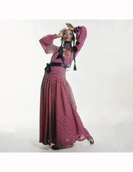 Model Kellie Wilson in gypsy-style Dior, wearing a long chiffon dress in lilac with white batik print, a ribbon belt and massive gold pendant Vogue October 01, 1969 Bert Stern