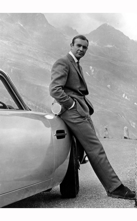 Sean Connery poses as James Bond next to his Aston Martin DB5 in a scene from the United Artists release 'Goldfinger' in 1964
