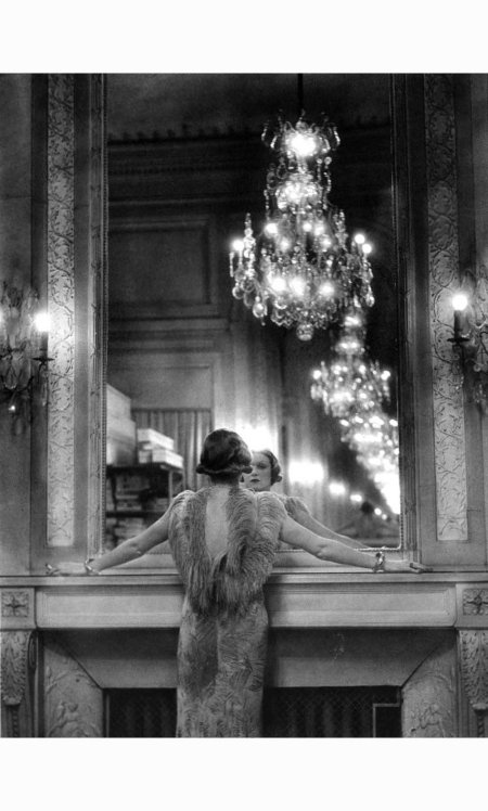 Alfred Eisenstaedt - Model in ostrich feather-trimmed gown pausing to regard herself in grand mirror of the Molyneux atelier. Paris, France, 1934