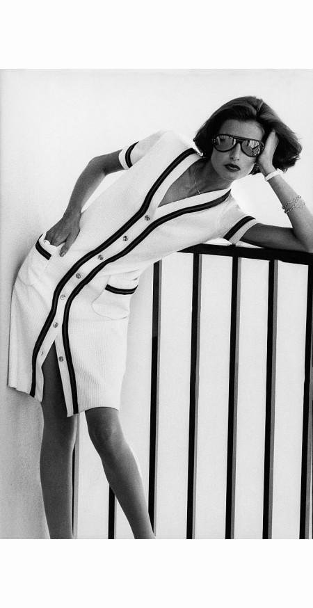 Apollonia wearing mirrored sunglasses and white cardigan-cut shirtdress by Patrick Porter for Adele Martin, leaning on railing at Xanadu Princess hotel, Freeport, Grand Bahama Vogue may 1973 © Bob Stone