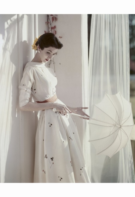 Dovima looking down, holding a parasol and wearing a flower-printed, collared dress with buttons down the center front, sashed at the waist © Horst.P Horst