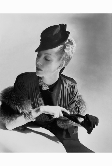 Helen Bennett in a draped crepe dress with pleats falling from the yoke. A fur stole, black gloves, bracelets, and a jeweled clip at the throat finish her elegant vogue-july-1938