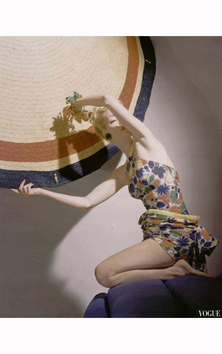 Helen Bennett with garland in one hand and umbrella in other, wearing multicolored cotton print bathing suit with a draped bustle Vogue Dec 1939 © Horst P.Horst
