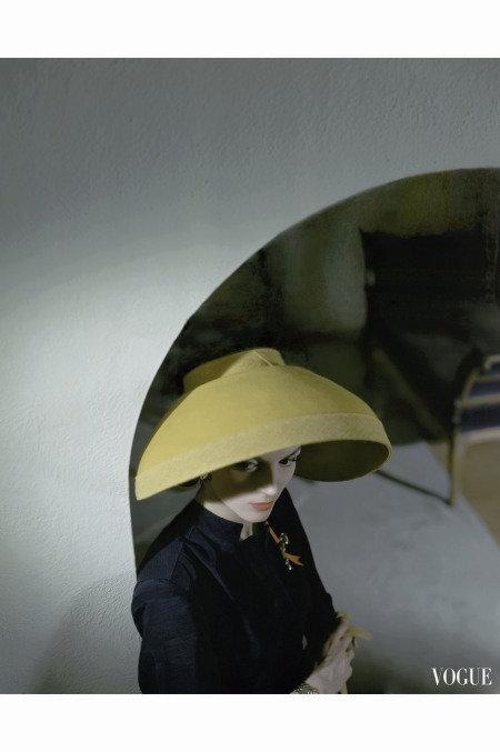 Model in archway wearing wide yellow felt scoop bonnet from John Frederic vogue june 1943 © Horst P Horst