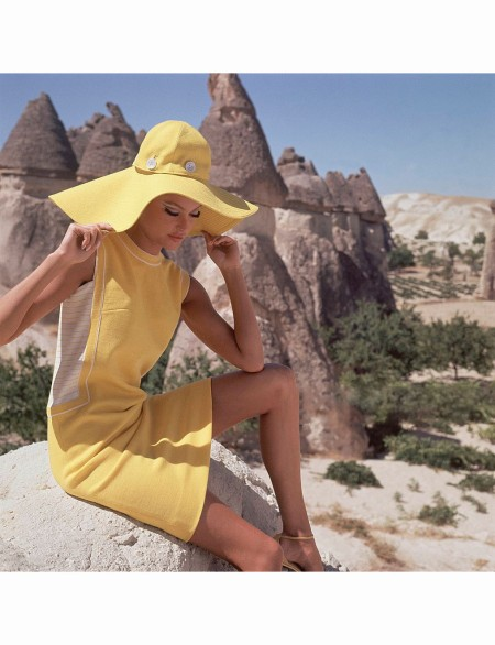 Model in Goreme, Turkey, wearing bright yellow dress with yellow and white striped side panels by Leslie Fay Dec 1966