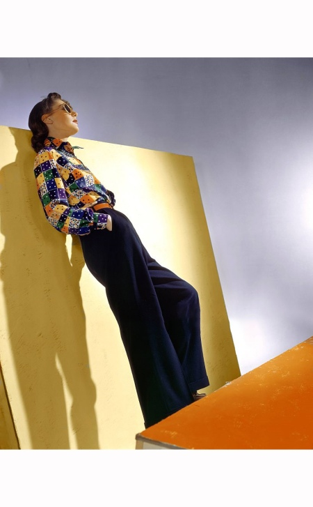 Model in sunglasses wearing country flannel slacks, and a multi-colored foulard shirt Vogue 1939