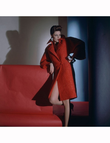 Model Leticia Lucas leaning on her elbow with her hand on her hip and her right leg bent, and wearing a red silk cloque evening overcoat by Galanos with earrings and a bracelet by Linda Charlop