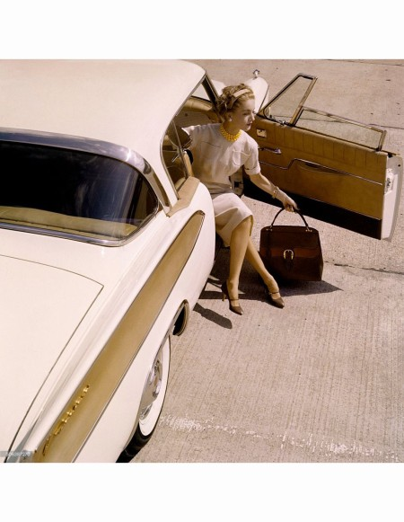Model seated in the open doorway of a 1958 Packard Hawk, in a beige dress by David Goodstein, with pearls from Verdura and a Gucci travel handbag © Karen Radkai