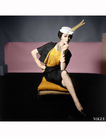 Model seated on yellow cushion, wearing black silk shantung suit with yellow blouse with white spots, by Adele Simpson Vogue 1961