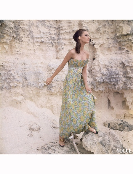 Model standing amongst light colored rocks wearing pin pleated evening gown, strapless fan pleated top with wide waist band and spaghetti tie, in pale flowered print on Dacron and cotton, by Mollie Parnis