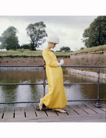Model standing on planks beside moat at Kronberg, Denmark, wearing evening coat of yellow matelasse by Mollie Parnis, and white gloves Vogue 1964 © Horst P. Horst