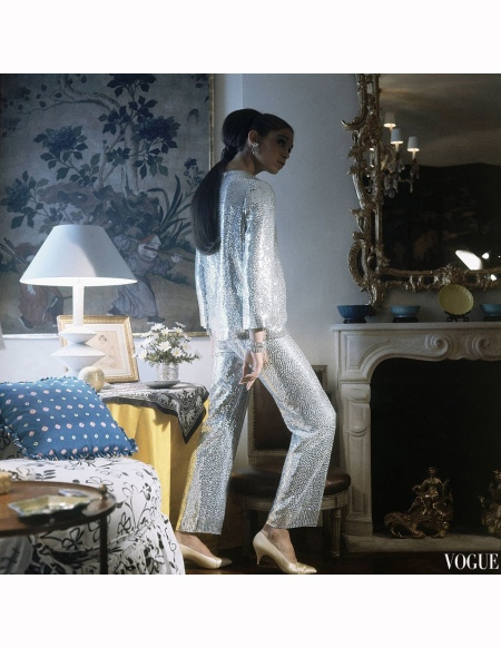 Model stands wearing silvery pyjamas by Norell; earrings by Schreiner and satin pumps by Belgian in the home of Norell surrounded by antiques; Hair by Suga of Kenneth Vogue Nov 1966 © Horst P. Horst