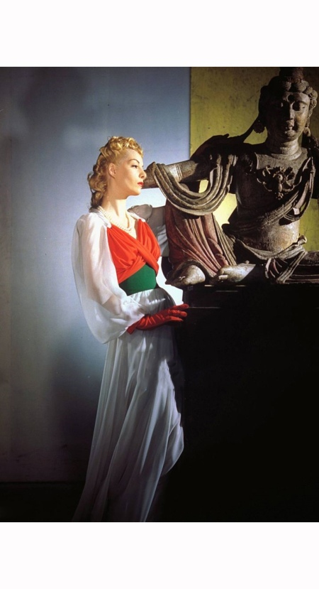 Model, wearing a white chiffon dress with a red and green halter bodice and red gloves, standing next to Asian statue Vogue 1940 © Horst P. Horst