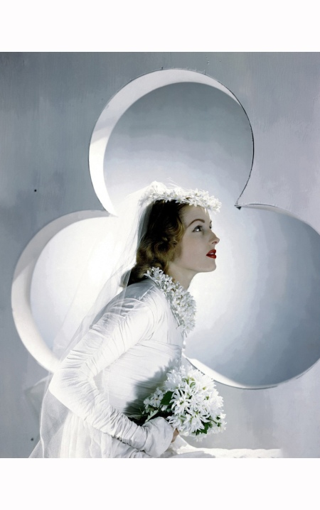 Model wearing bridal gown with orange-blossom crown, necklace, and bouquet, with clover-shaped portal as background Vogue april 1941 © Horst P. Horst