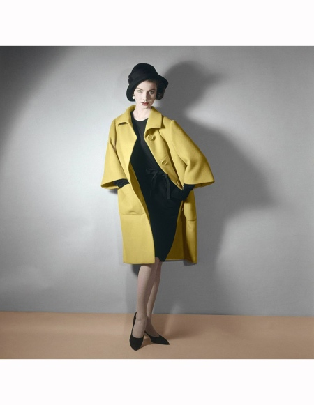 Model wearing bright yellow coat over black dress with black hat, by Norman Norell Vogue 1961
