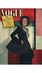 Model wearing dark blue suit with rayon taffeta bow, black fox hat and muff, standing against colorful geometric background Vogue October 15 1942 © Horst P.Horst cover