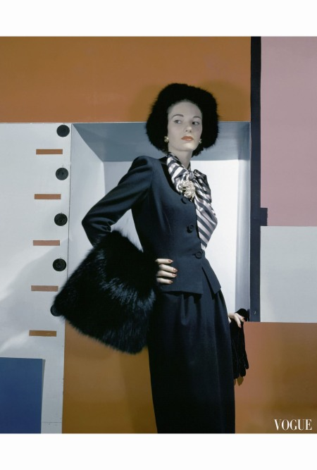 Model wearing dark blue suit with rayon taffeta bow, black fox hat and muff, standing against colorful geometric background Vogue October 15 1942 © Horst P.Horst
