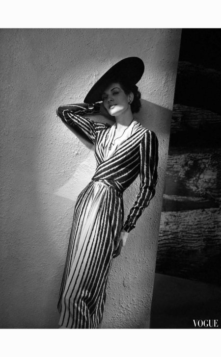 Model wearing long zebra-stripe dress with crossed bodice by Lucien Lelong, jewelry by Bijoux Boucheron, and wide flat hat. Vogue - March 1938 © André Durst