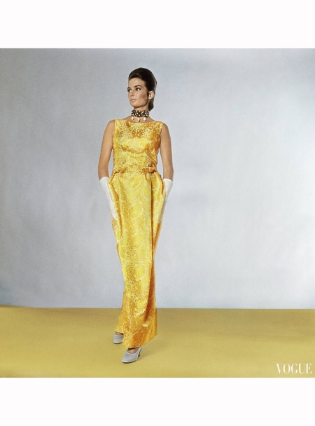 Mrs. Frederick Cushing wearing sleeveless dress of vivid yellow brocade, highlighted with white design, by Leslie Morris. Worn with collar of bogus jewelry and pear-shaped fake pearls oct Vogue 1963