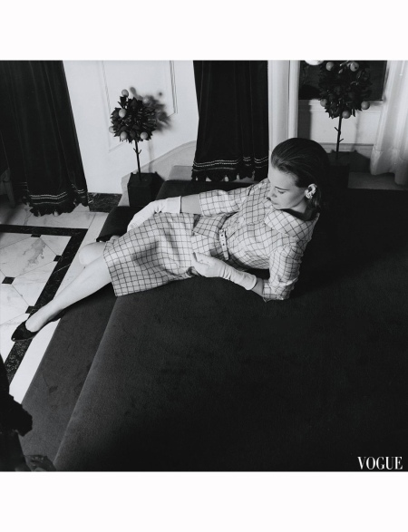 Mrs. Wyatt Cooper (aka Gloria Vanderbilt) at home, reclining on stairs and wearing a tattersall-check suit with three-quarter sleeves designed by Mainbocher; hair by Duval of Kenneth 1966 © Horst P. Horst