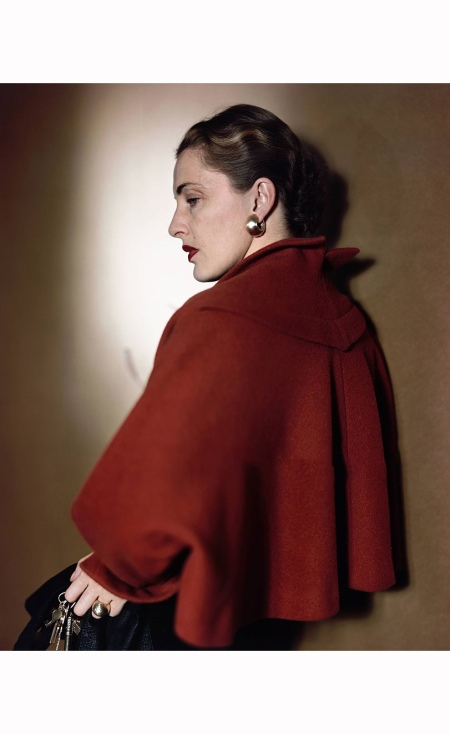 Nancy Slim Hawks Mrs. Howard Hawks, aka Slim Keith. She is wearing a red bolero capelet by Trigere, over a black sheath dress, Her back is facing toward the camera, showing the line of the jacket