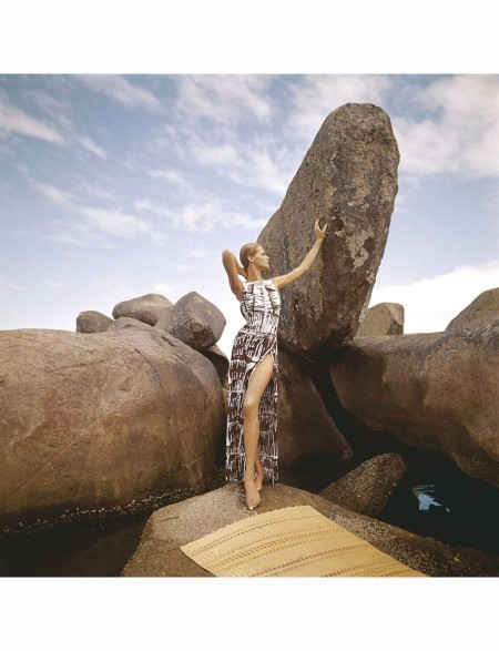 Veruschka at beach on large rocks wearing Galitzine maillot in white with brown print and matching skirt in the reverse pattern with deep side slit Vogue 1965 © Henry Clarke
