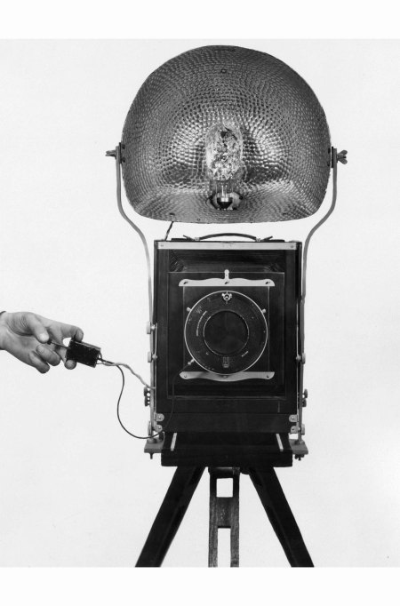 A hand operating the Sashalite system, an early type of flashbulb invented by British photographer Alex 'Sasha' Stewart. A reflector spreads the light produced by the bulb. (Photo by Sasha:Getty Images)