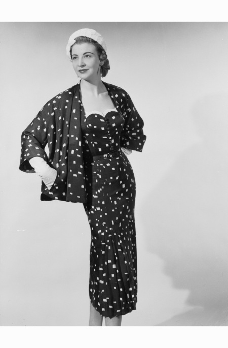 A woman modelling a Roucet et Cie fitted dress, with a pleated skirt, and a loose matching jacket in a dark material with a pale flecked design 1954 chaloner-woods-speckled-suit