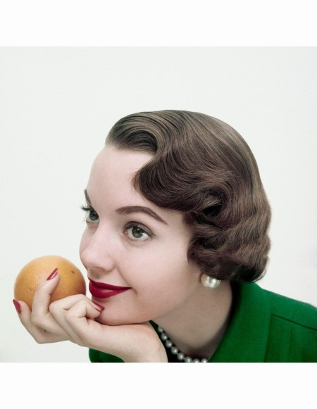 Close-up of model holding orange close to mouth, with makeup by Revlon Glamour 1955