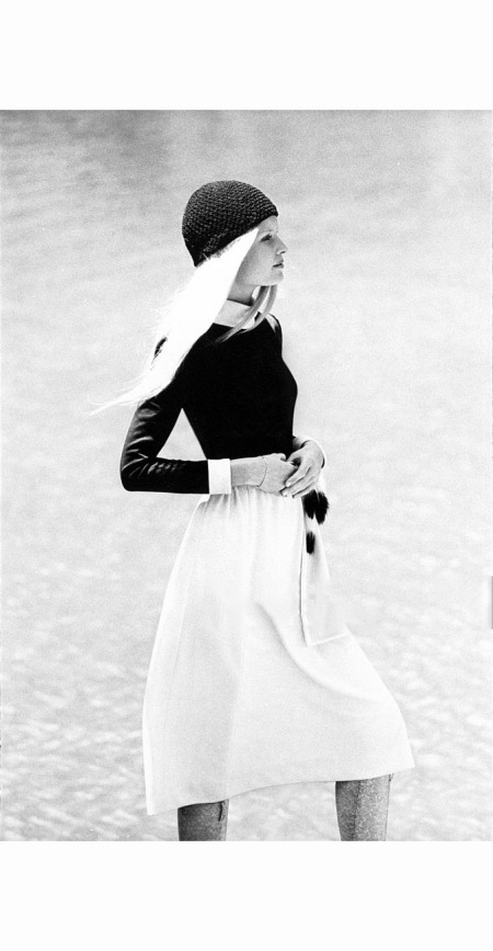 Gunilla Lindblad wearing a black top with white collar and cuffs with a white skirt by Nardis of Dallas and a black knit skull cap by Halston, she stands with both hands on her abdomen 1970 © J. P. Zachariasen