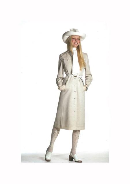 Gunilla Lindblad wearing beige wool knit coat by Calvin Klein, beige hat by Madcaps, Elegant belt, Aris gloves and Gucci watch and bracelets 1971 © Gianni Penati