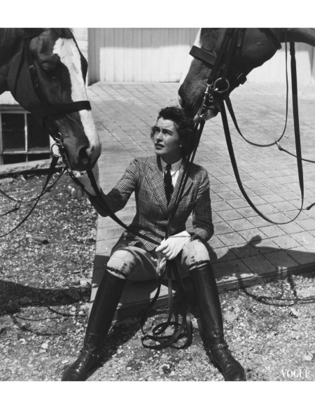 Mary Goetchius, wearing a checked cotton riding jacket, jodhpurs, and black, knee-high riding boots, sitting on a tiled terrace and holding the reins of two horses toni-frissell-vogue-july-1938