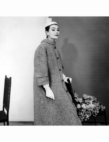 Model Anne Gunning wearing a tweed coat with pockets on the sleeves by Balenciaga, with a hat and gloves 1954