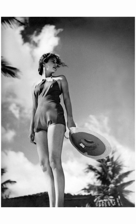 Model, in a one-piece bathing suit in perforated dark rubber, with rope back straps, standing on a beach holding a wide-brimmed straw hat Vogue 1935 © Toni Frissell