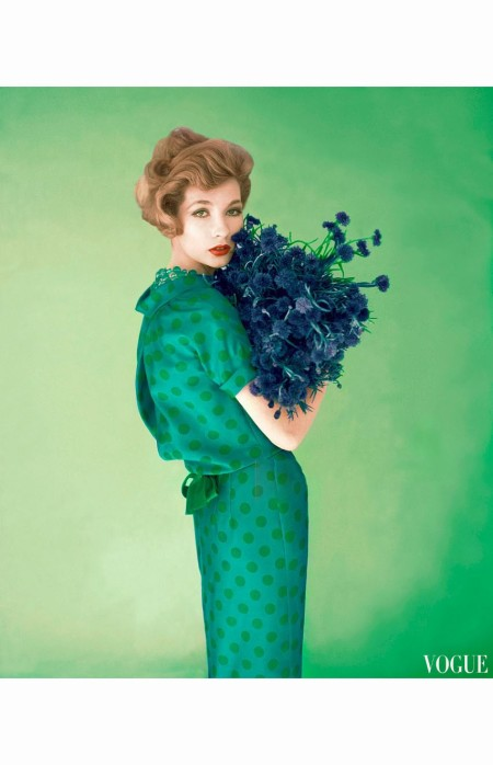 Model in couture silk blue dress with green polka-dots by Dan Keller, holding bundle of wild flowers Vogue 1958 © Leombruno Bodi