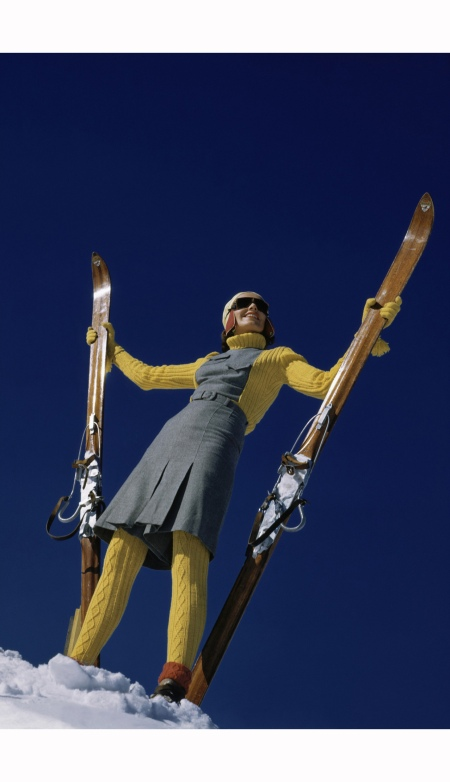 Model in yellow-and-gray ski suit, standing with skis in snow Vogue Jan 1941 © Toni Frissell