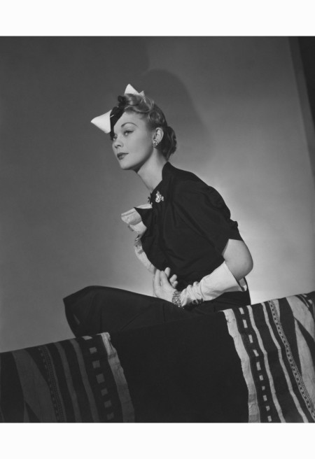 Model (Lind) wearing small, folded hat with large white bow on the side, and short-sleeved, black crepe dress with white ruffles down the bodice front, both by Patou horst-p-horst-vogue-march-1938