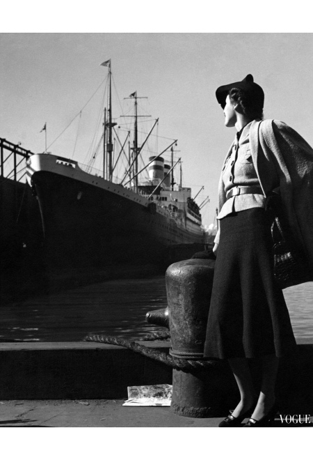 Model, standing at a port with the ocean liner Hansa in the background, wearing a wool mesh cape over a belted jacket, dark blouse and skirt, and holding a black alligator bag by Koret toni-frissell-vogue-december-1936