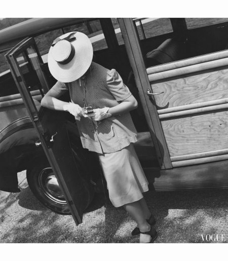 Model, standing near a car door, lighting cigarette, and wearing a maternity suit in chartreuse Porella, with a dot pint top, and a wide-brimmed straw hat. toni-frissell-vogue-july-1939-1
