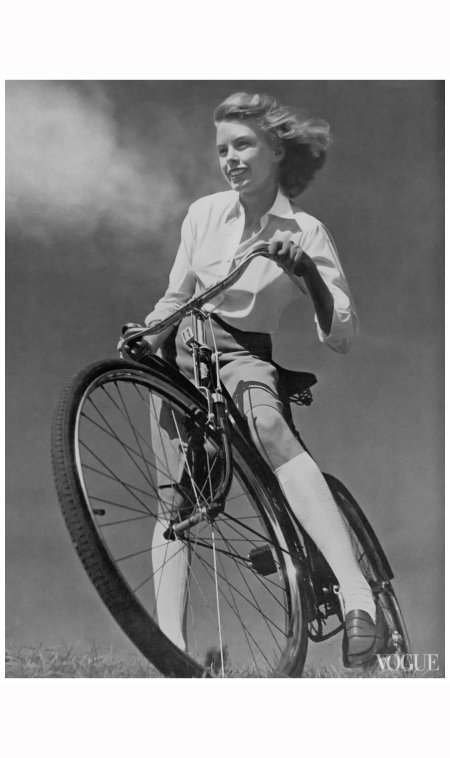Model wearing a white shirt, skirt, and knee-high socks with penny loafers, standing astride a bicycle on a hilltop Vogue, May 15, 1942 © Toni Frissell